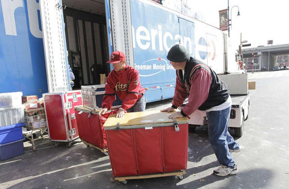 Batboy Patrick Eaves, left, and Chris Clarke haul away baseball equipment to be stored in the truck. Photo: Karen Warren, Chronicle