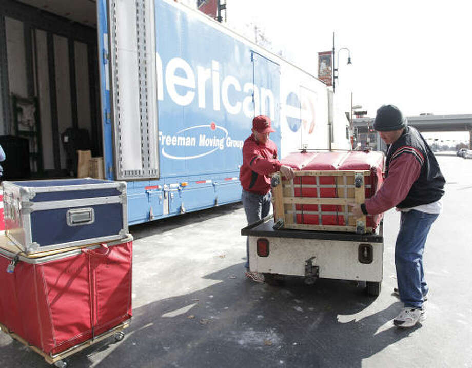 Batboy Patrick Eaves, left, and Chris Clarke haul baseball equipment into a moving truck. Photo: Karen Warren, Chronicle