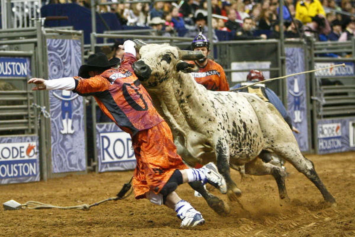 A rodeo clown tries to distract a bull during the PRCA Xtreme Bull Riding event that closes out the 2010 Houston Livestock Show and Rodeo Houston at Reliant Park.