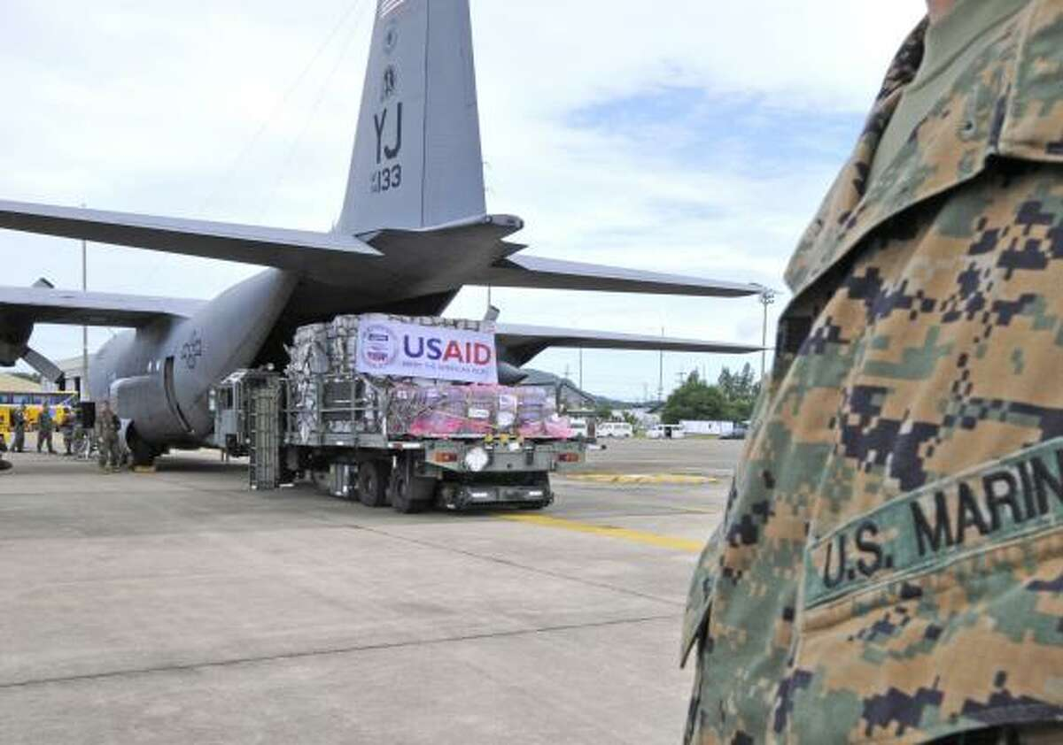 U.S. military personnel load relief supplies onto a C-130 transport plane at a Thai air force base for delivery to Myanmar. Chevron says it is using its presence in the country to deliver aid to victims of the tropical cyclone.