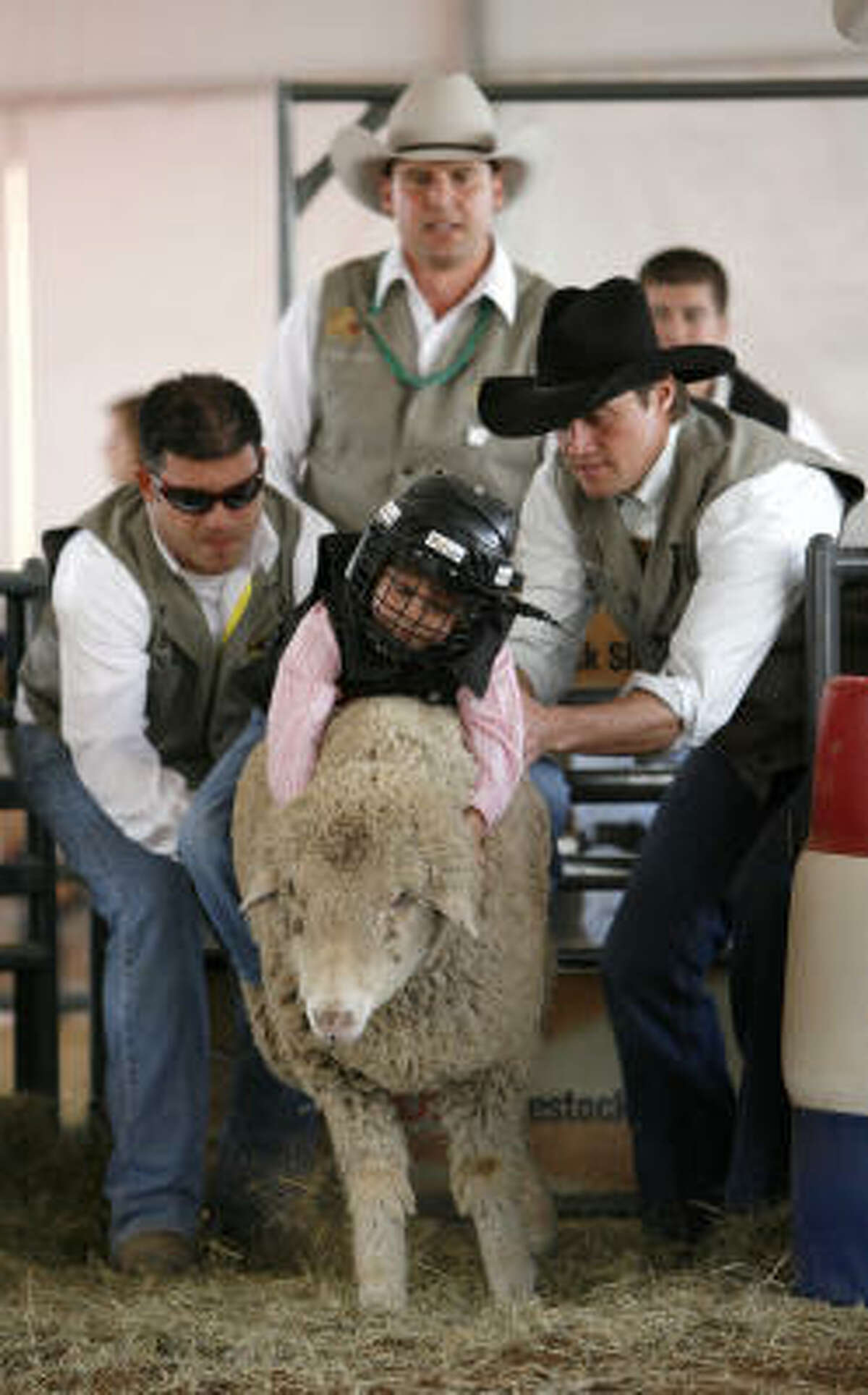 Sarah Schwarzbach, of Houston, gets some help coming out of the chute during the Mutton Bustin' in Kids Country at the Houston Livestock Show and Rodeo.