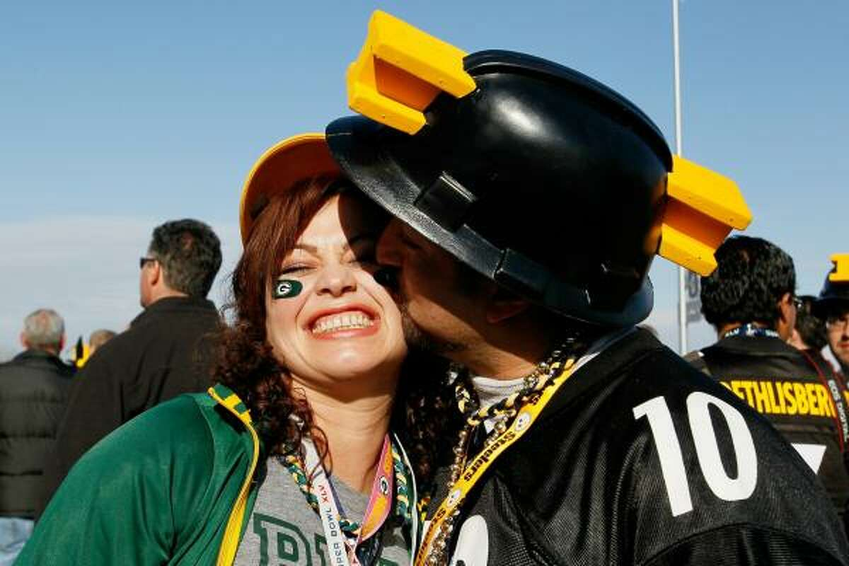 A Steelers fan kisses a Packers fan prior to Super Bowl XLV.