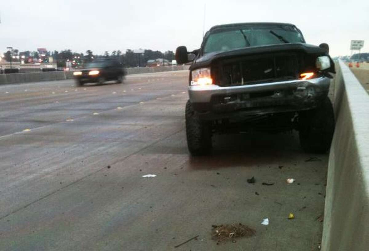 A truck sits abandoned on I-45 southbound after apparently hitting the retaining wall crossing the 105 bridge in Conroe.