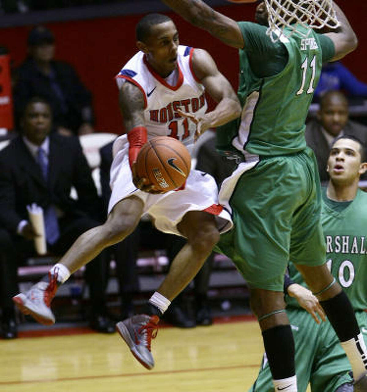 UH guard Darian Thibodeaux looks to make a wrap-around pass past Marshall center Nigel Spikes in the first half.