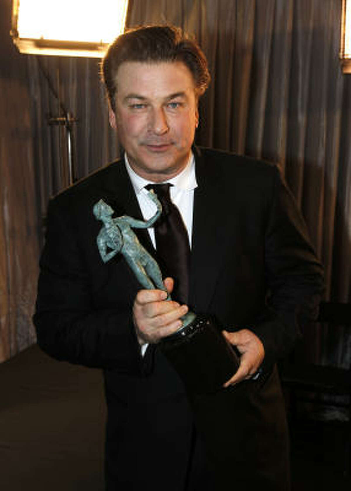 Alec Baldwin should consider upsizing his shirts. A little snug around the neck.