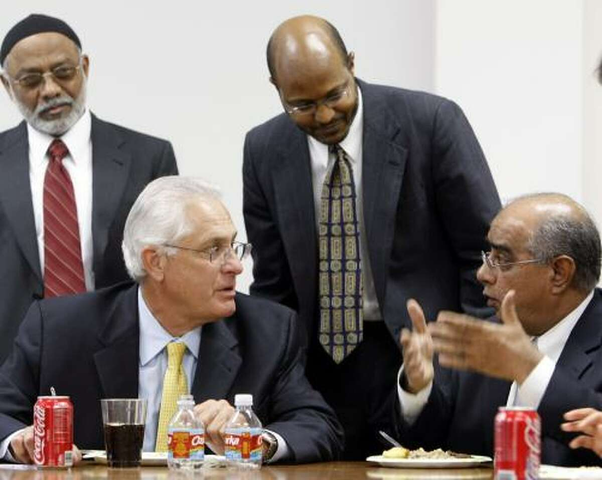Syed Naiyer Izfar of the Islamic Society of Greater Houston, right, explains his concerns to Sheriff Tommy Thomas at a meeting Monday that included Hashim Badat, left, the group's vice president, and its president, Rodwan Saleh.