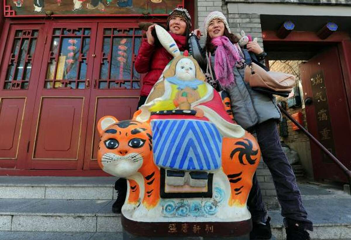 Women pose with a statue of Lord Rabbit at Bannerman Tang's Toys and Crafts, a shop in a quiet lane near the Confucius Temple in Beijing. The mythical bunny sent down from the moon to bring good health to Beijing, is making a triumphant comeback as the Chinese capital gears up for the Lunar New Year, which begins on Feb. 3.