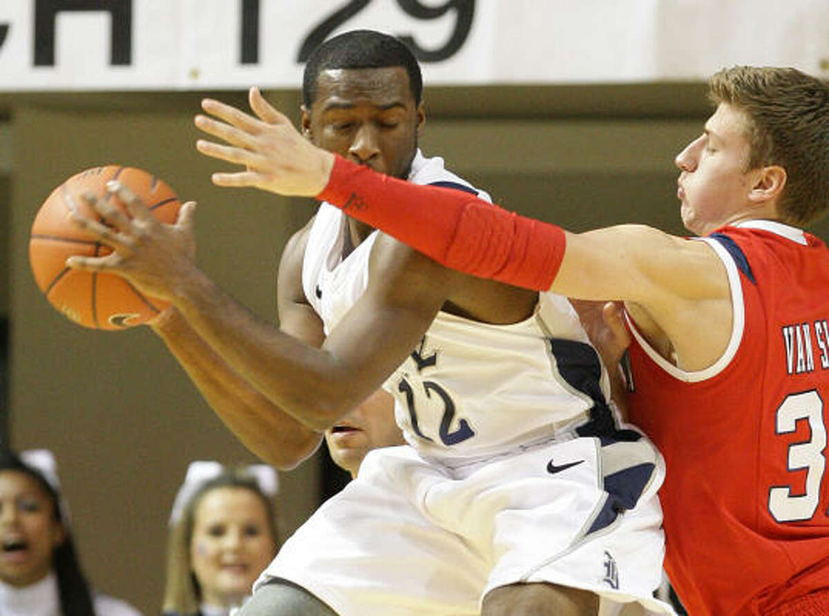 Owls guard Bryan Beasley (12) grabs a rebound in front of Houston forward Kirk Van Slyke.