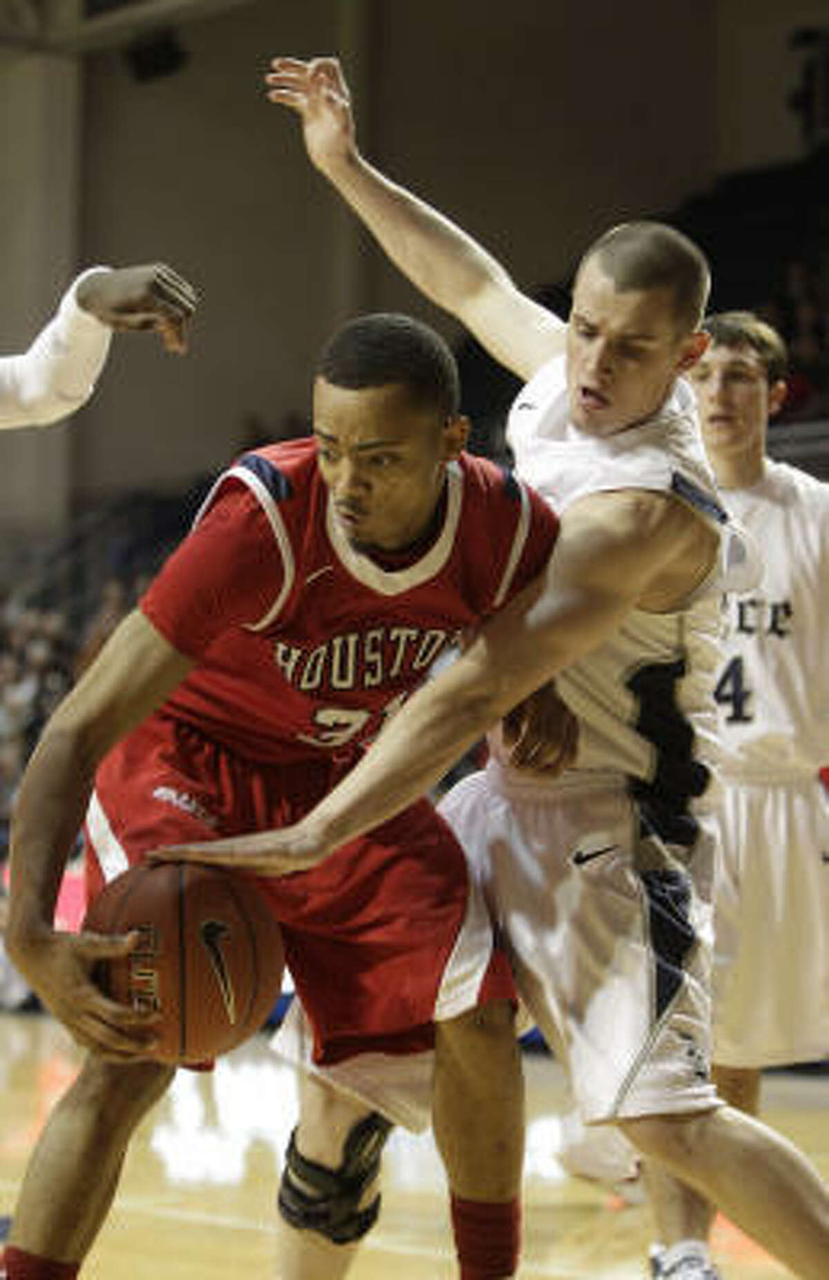 Houston guard Adam Brown (31) battles with Rice guard Cory Pflieger (32) for the ball.