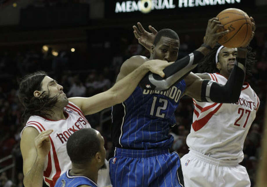 Jan. 22: Magic 118, Rockets 104 Rockets forward Luis Scola, left, fouls Magic center Dwight Howard (12) during the second half. Howard torched the Rockets for 22 points and 14 rebounds to lead the Magic to a convincing victory Saturday night at Toyota Center. Photo: Pat Sullivan, AP