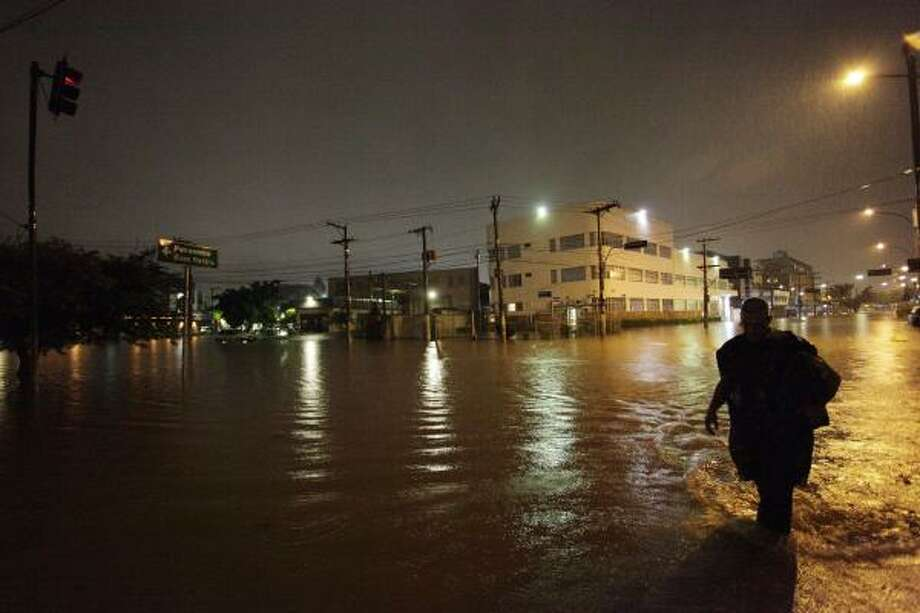 A man walks through a flooded street after heavy rains in Barra Funda, Sao Paulo, Brazil. Brazilian authorities say heavy rains have triggered mudslides and floods in southeastern Brazil, killing at least 13 people. Sao Paulo state civil defense officials say 11 people died when their houses collapsed because of mudslides and two were killed in flash floods. Photo: Nelson Antoine, AP