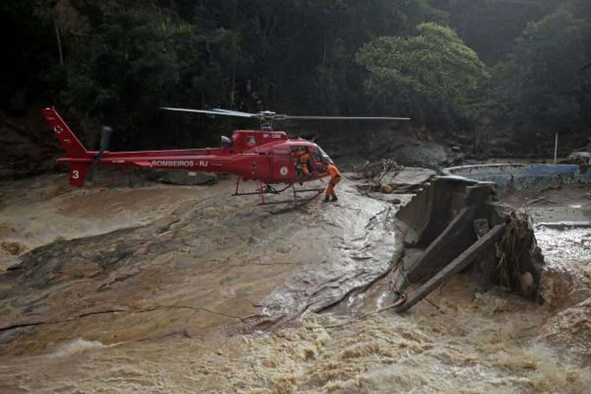 Rescue workers get on a helicopter as they leave after searching for survivor and victims in an area affected by a landslide near Nova Friburgo, Brazil.
