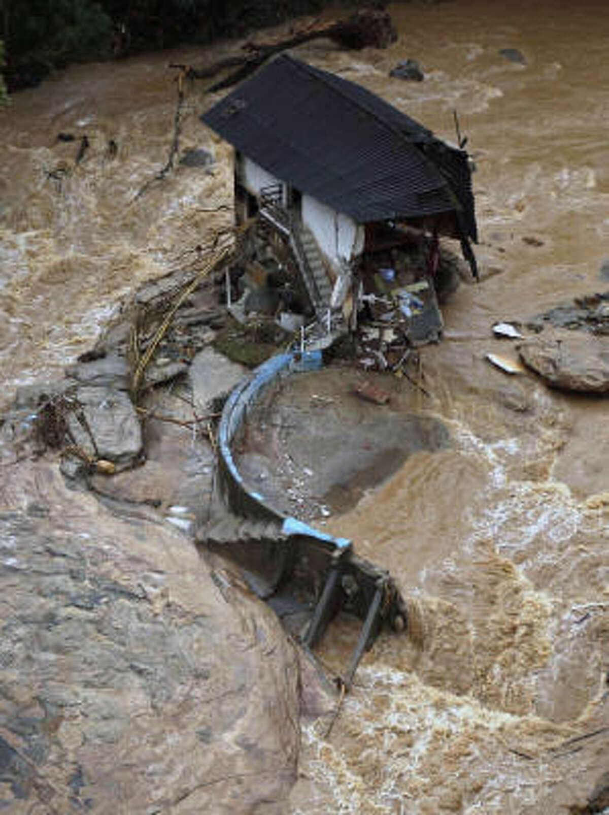 A damaged house surrounded by flooding in seen in an area affected by a landslide in Nova Friburgo, Brazil.