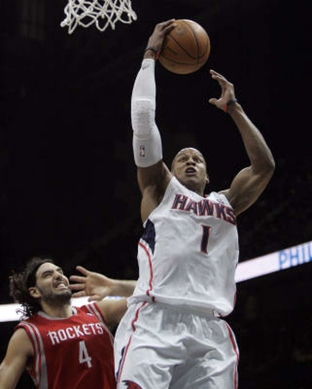 Hawks small forward Maurice Evans (1) beats Rockets forward Luis Scola to the basket in the first half.