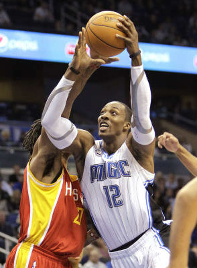 Magic center Dwight Howard (12) gets off a shot past Jordan Hill. Photo: John Raoux, AP