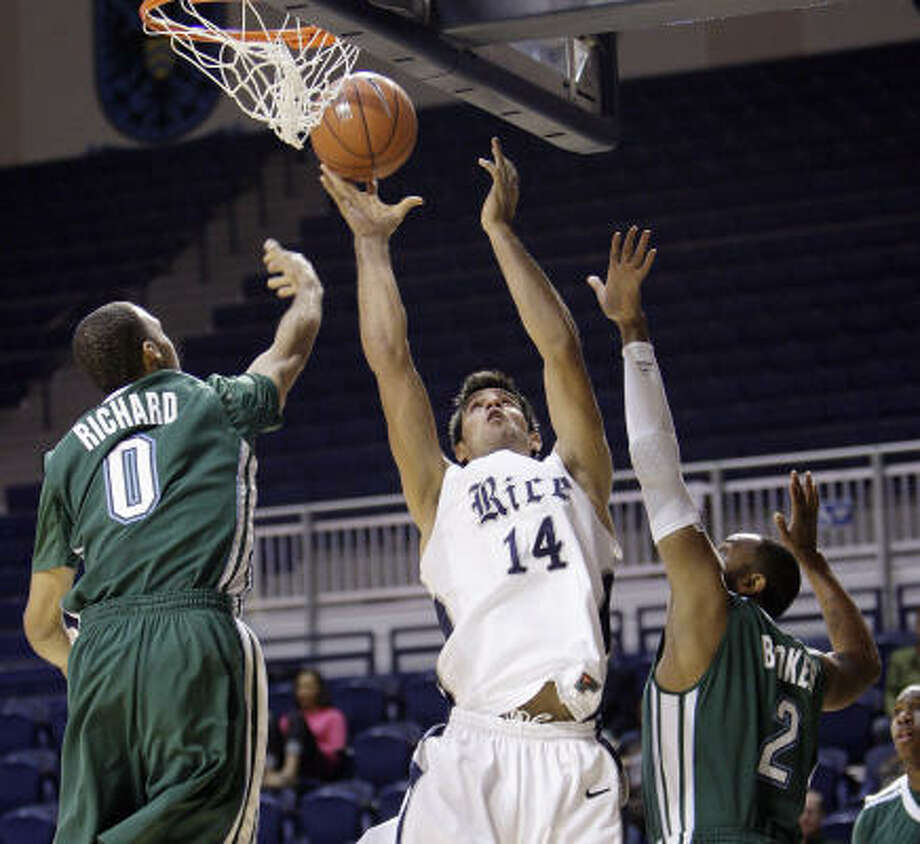 Rice's Arsalan Kazemi (14) puts back a shot over Tulane's Kris Richard (0) and David Booker. Photo: Bob Levey, For The Chronicle