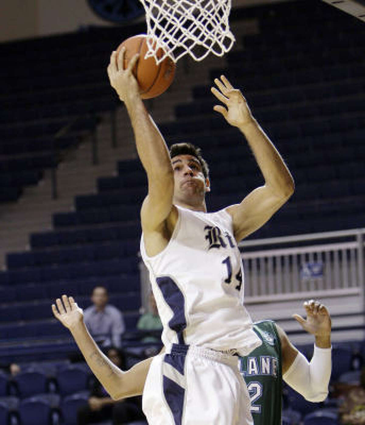 Rice's Arsalan Kazemi drives to the basket over Tulane's David Booker in the first half.