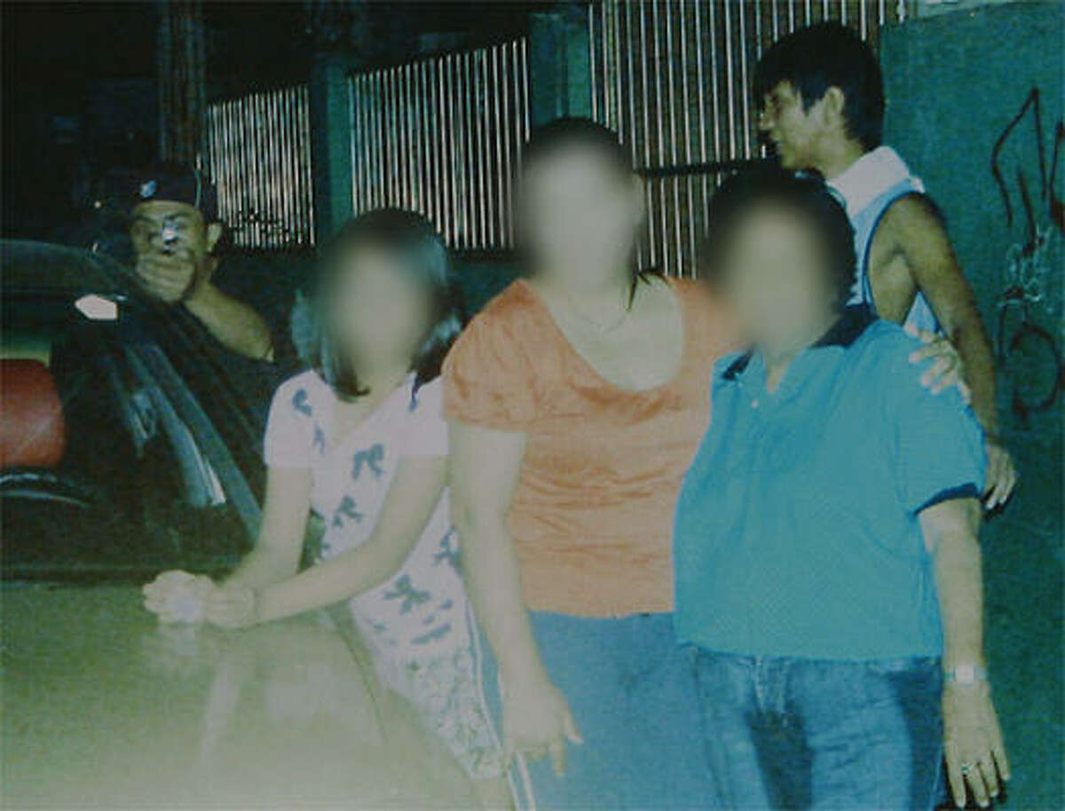 A reproduction of a handout photo released by the Dagsa family on Jan. 4, 2011, shows an alleged assassin (back left) pointing his gun towards politician councilor Reynaldo Dagsa who was taking a photo of family members on Dec. 31, 2010, while the alleged lookout (back right) stands behind. The murdered Philippine politician caught his killer on camera just moments before he was shot dead, with the photograph leading to the arrest of the gunman, police said. The faces are blurred at the request of the family. • See more photos from this story.