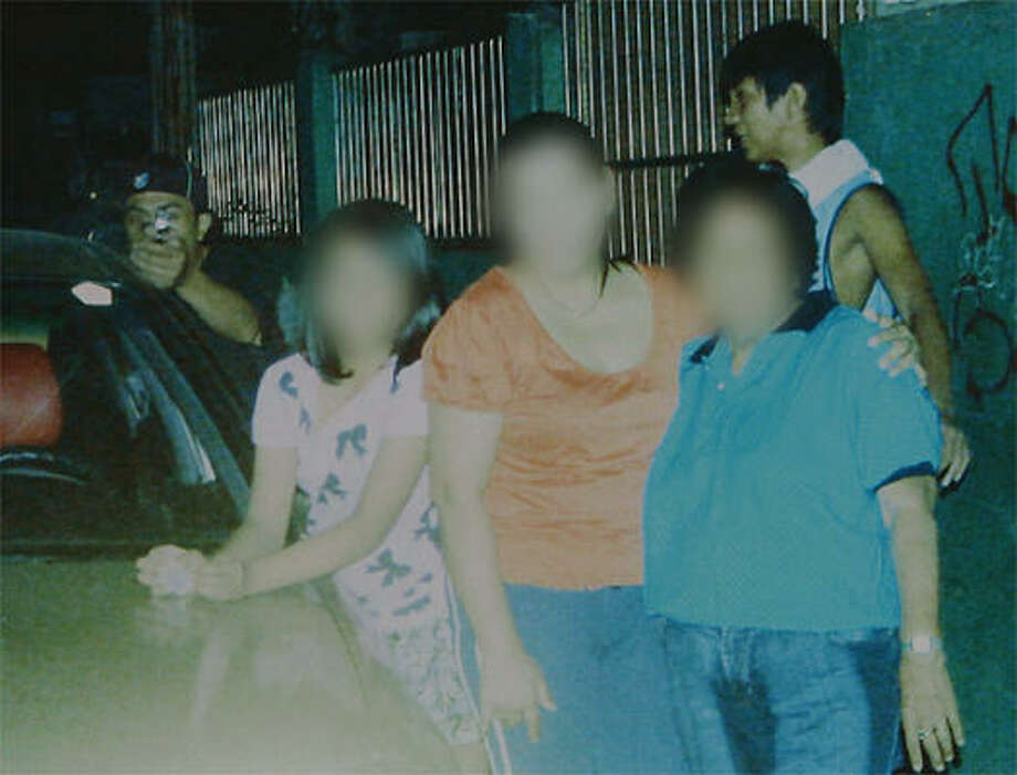 A reproduction of a handout photo released by the Dagsa family on Jan. 4, 2011, shows an alleged assassin (back left) pointing his gun towards politician councilor Reynaldo Dagsa who was taking a photo of family members on Dec. 31, 2010, while the alleged lookout (back right) stands behind. The murdered Philippine politician caught his killer on camera just moments before he was shot dead, with the photograph leading to the arrest of the gunman, police said. The faces are blurred at the request of the family. • See more photos from this story. Photo: AFP PHOTO / HO / Dagsa Family