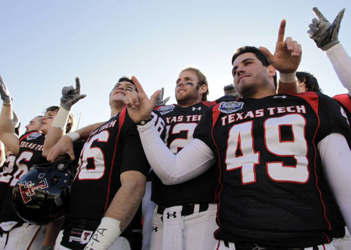 Texas Tech wide receiver Alexander Torres (86), quarterback Taylor Potts (12) and kicker Donnie Carona (49) sing the school song as they celebrate their win in the TicketCity Bowl.