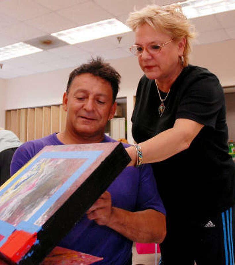 Instructor Salli Babbitt helps Ramiro Bermudez on a painting during a Healing Art class at the West Gray Adaptive Recreation Center, 1475 W. Gray.