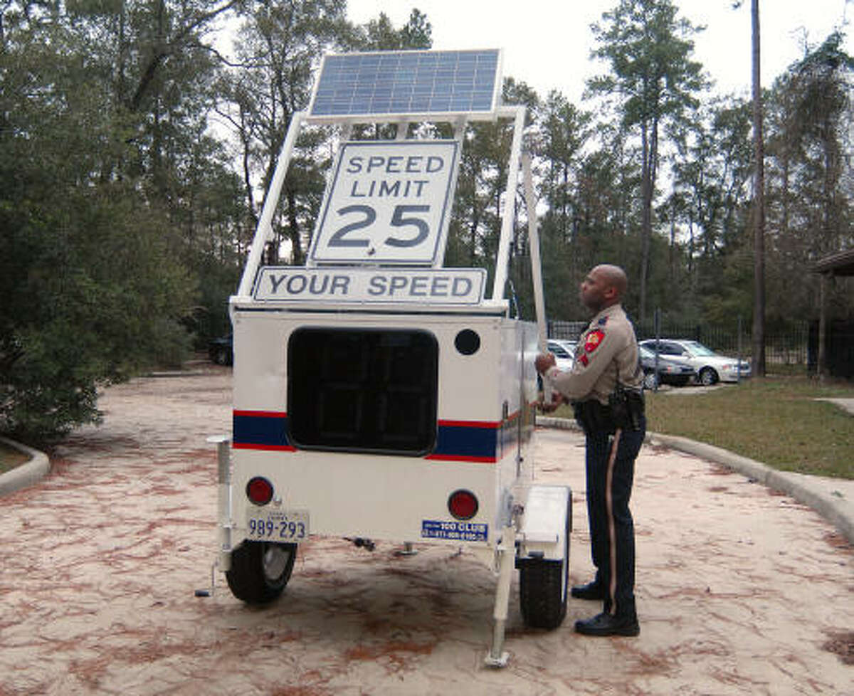 Montgomery County Sheriff's Department Cpl. Jermaine Jenkins sets up the sheriff's department speed tracker trailer in The Woodlands. The machine is used to measure a vehicle's speed.