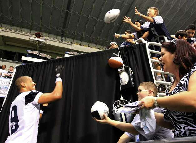 Receiver Miles Austin throws an autographed football back to a young fan at the conclusion of the afternoon session of the first practice of the Dallas Cowboys training camp at the Alamodome on Thursday, July 28, 2011. Kin Man Hui/kmhui@express-news.net Photo: KIN MAN HUI, : / SAN ANTONIO EXPRESS-NEWS