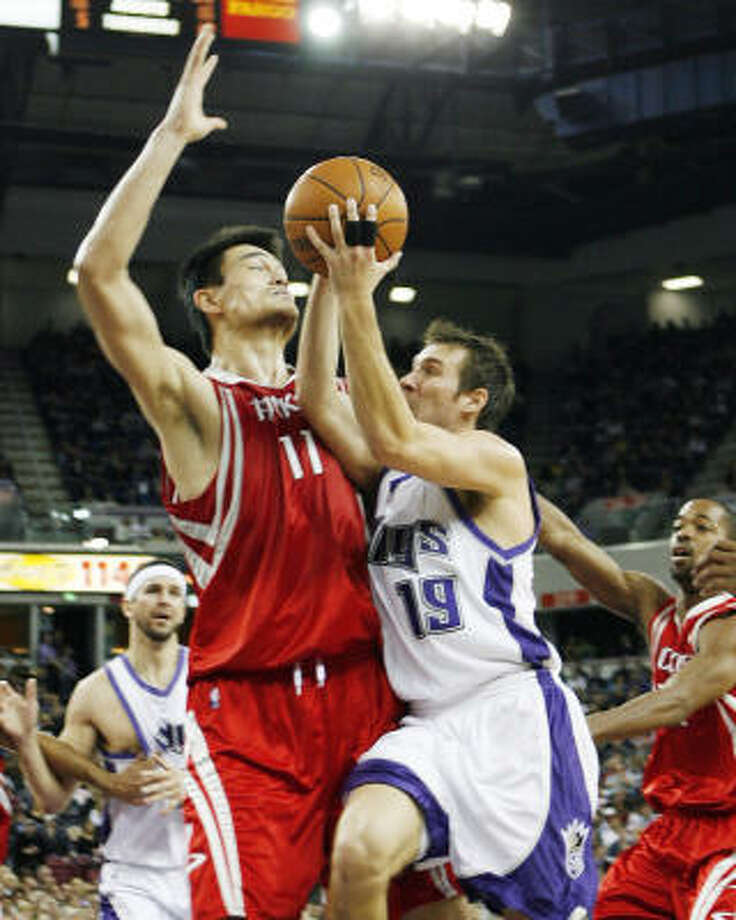 With Beno Udrih driving, Yao Ming draws his sixth foul in the loss to the Kings. Photo: Thearon Henderson, AP