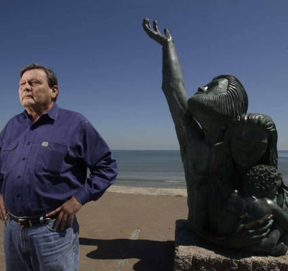 Flanked by the memorial to the Great Storm of 1900, oceanographer William Merrell dreams of a protected coast. Photo: Melissa Phillip, Chronicle