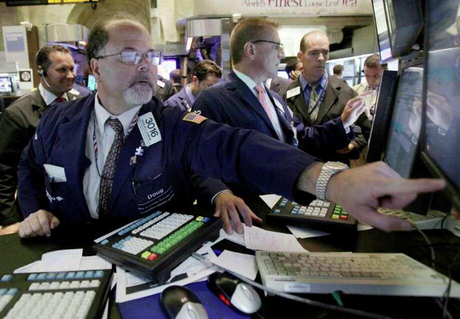 Specialists Douglas Johnson, left, and Scott Wetzel work at their post on the floor of the New York Stock Exchange Thursday, July 28, 2011. (AP Photo/Richard Drew) Photo: Richard Drew