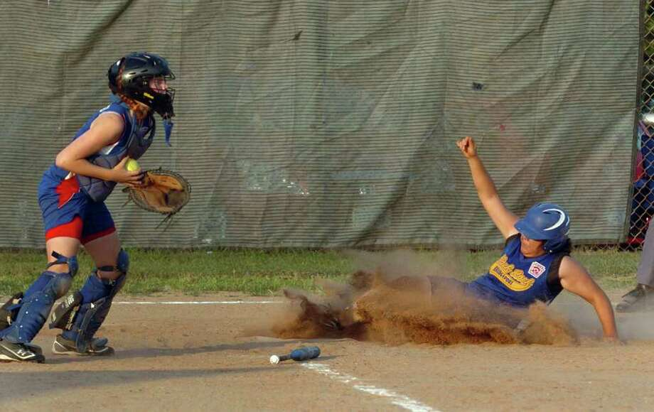 Black Rock's #41 Karla Grajeda slides into home plate before Waterford's Sarah Pacheero can make the tag, during little league softball championship action in West Haven, Conn. on Thursday July 28, 2011. Photo: Christian Abraham / Connecticut Post