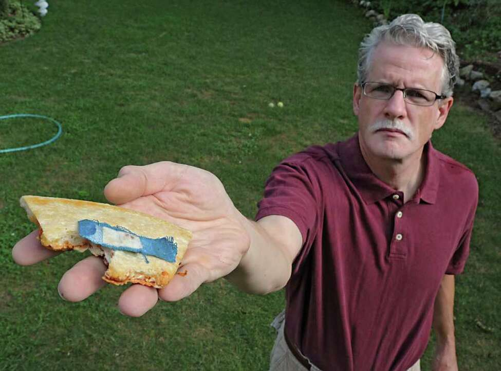 Ken Wieczerza holds a piece of Pizza Hut pizza with a bloody band-aid he found on it while taking a bite of the pizza at his home in Ballston Lake, N.Y. on Thursday, July 28, 2011.(Lori Van Buren / Times Union)