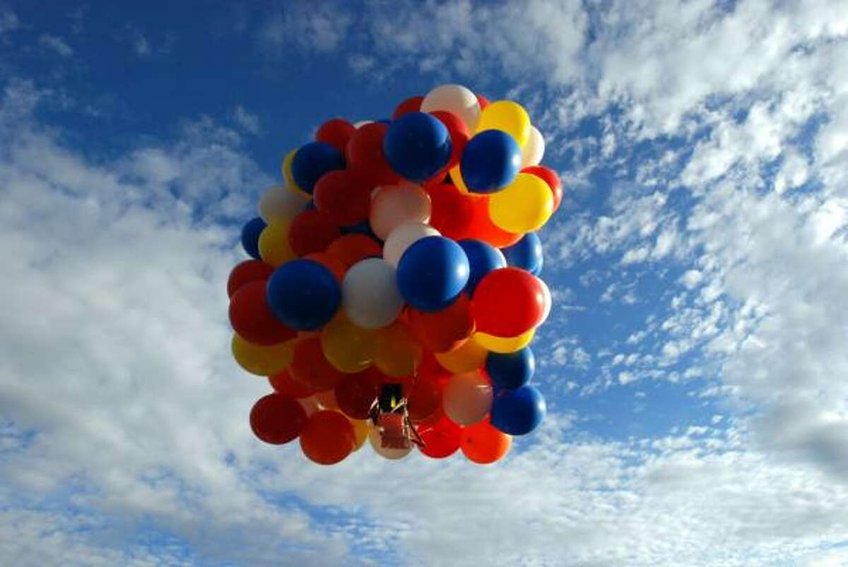 Kent Couch leaves his gas station in Bend, Ore., on Saturday riding a lawn chair rigged with more than 150 giant helium-filled balloons in an attempt to fly to Idaho.