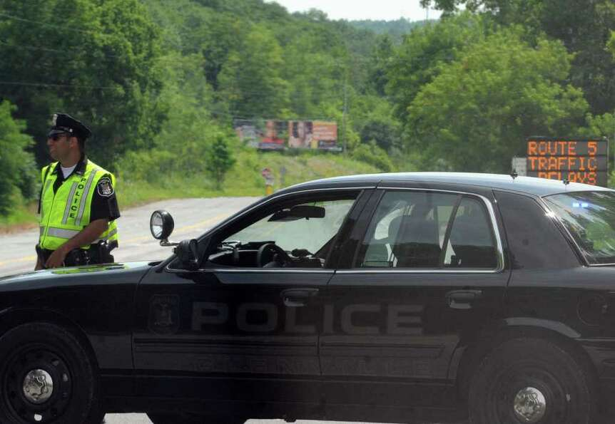A Glenville Police Officer holds diverts traffic from a portion of Route 5 during filming of the mov