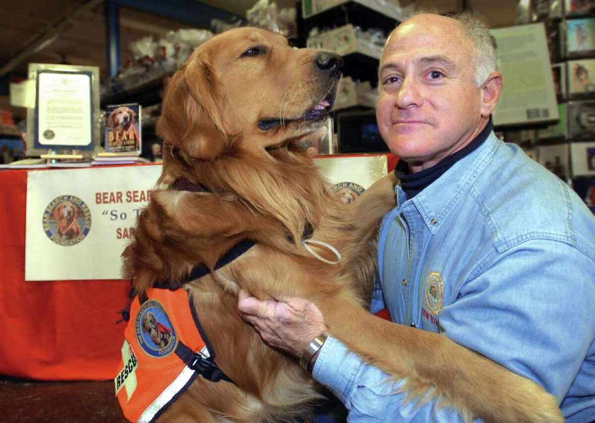 In this 2005 file photo, Theodore, left, a son of Bear, with his owner, Scott Shields. Scott Shields defrauded the federal government out of thousands of dollars after claiming he and Bear recovered bodies at ground zero in the wake of the Sept. 11, 2001, attacks.
