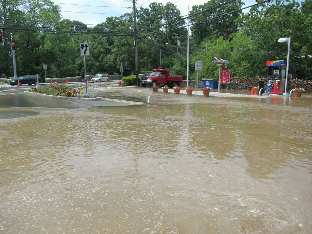 A water main break sent a torrent of water gushing onto Glenville Road at Riversville Road in western Greenwich around midday Thursday, closing the busy intersection and cutting water off to Glenville residents. Photo by Salvatore Scalisi