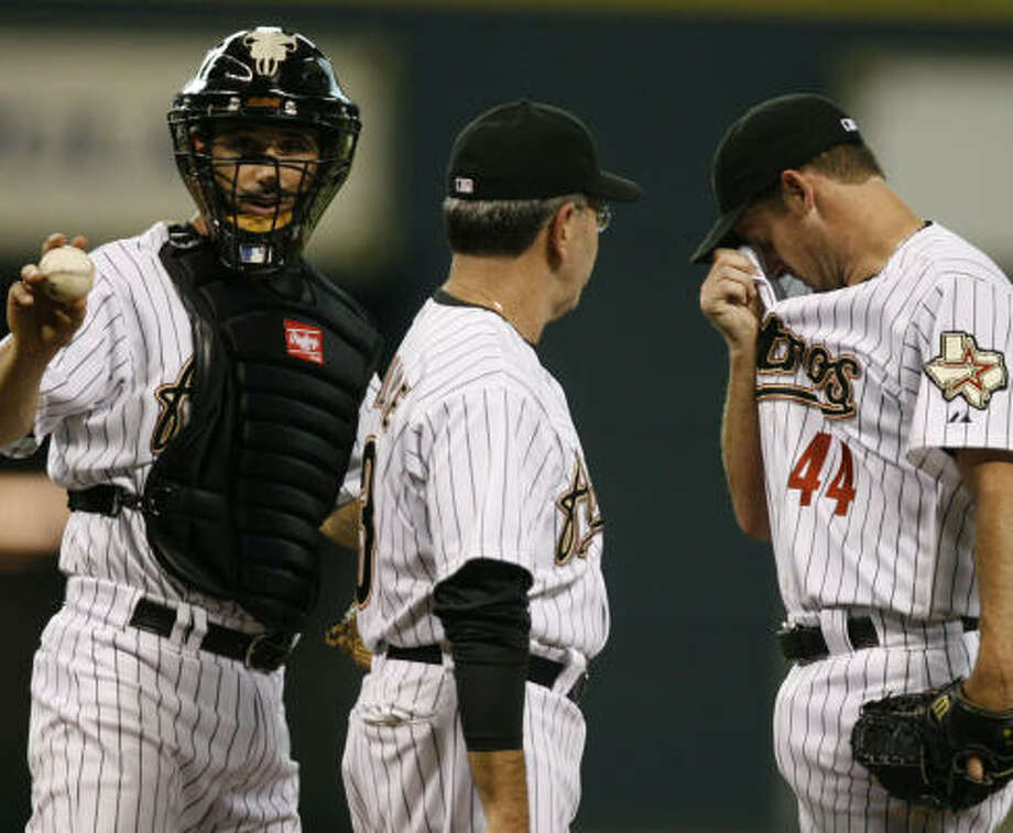 Oakland's three-run second inning prompted a meeting on the mound for Brad Ausmus, pitching coach Dave Wallace and Roy Oswalt. Photo: Melissa Phillip, Chronicle