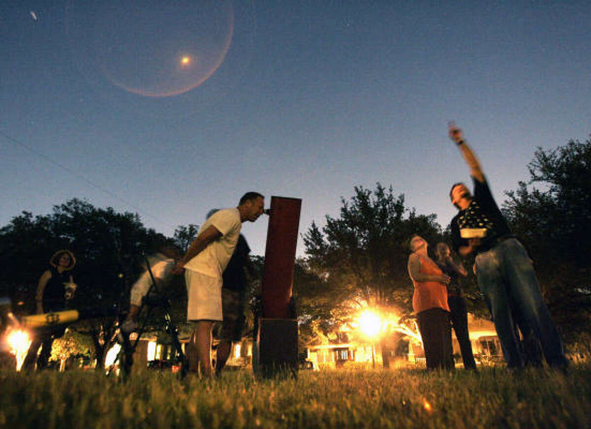 Michael Brewster takes his turn at the telescope on the Norhill Esplanade as Ken Fraley points out key objects in the sky.