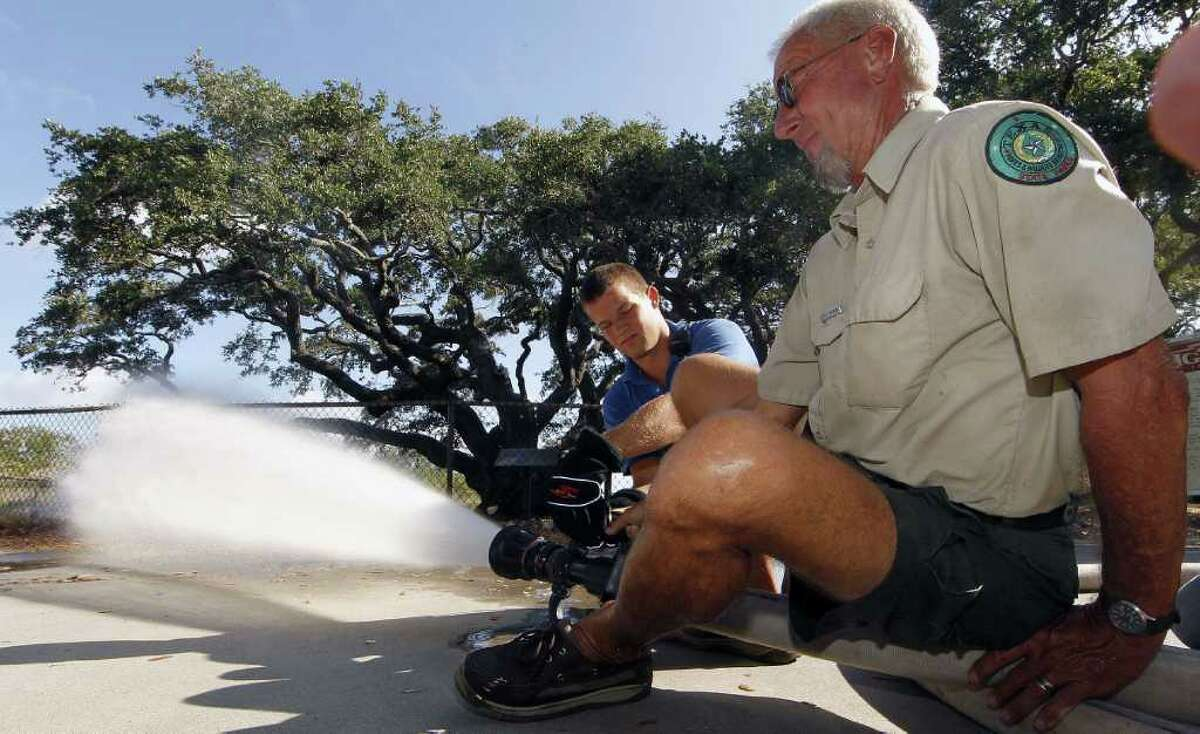 Fulton volunteer firefighter Matt Wright and Bill Wilson of the Texas Parks & Wildlife Department use a fire hose to soak the Big Tree with 13,000 gallons of water, enough to simulate a half-inch of rain.