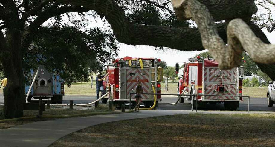Firetrucks from the Lamar, Fulton and Rockport volunteer fire departments haul water to the Big Tree at Goose Island State Park, about 25 miles northeast of Corpus Christi. Photo: AP Photo/Corpus Christi Caller-Times, Todd Yates