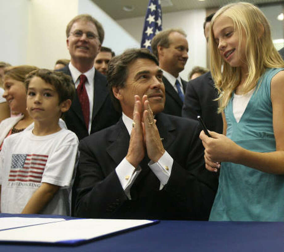 Lindsey Tredway, 9, joins Gov. Rick Perry after a signing ceremony on Tuesday at Clements High School in Sugar Land. The bill provides a model policy that schools may adopt. Photo: Billy Smith II, Chronicle