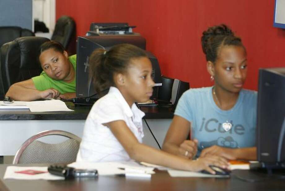 "Shawn Gordon, left, keeps an eye on nieces Sade Evans, 12, and Keva Provost, 12, whom she is home schooling at her office, along with her two daughters, who felt sick after attending Key Middle School. Gordon called the move to Fleming ""a wonderful idea."" Photo: STEVE CAMPBELL, CHRONICLE"