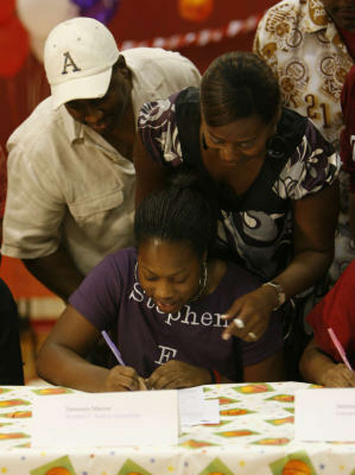 Tammara Marion, center, signs her letter of intent to play basketball at Stephen F. Austin, with her parents Jacqueline and Tyrone Marion watching during signing day at Bellaire High school.