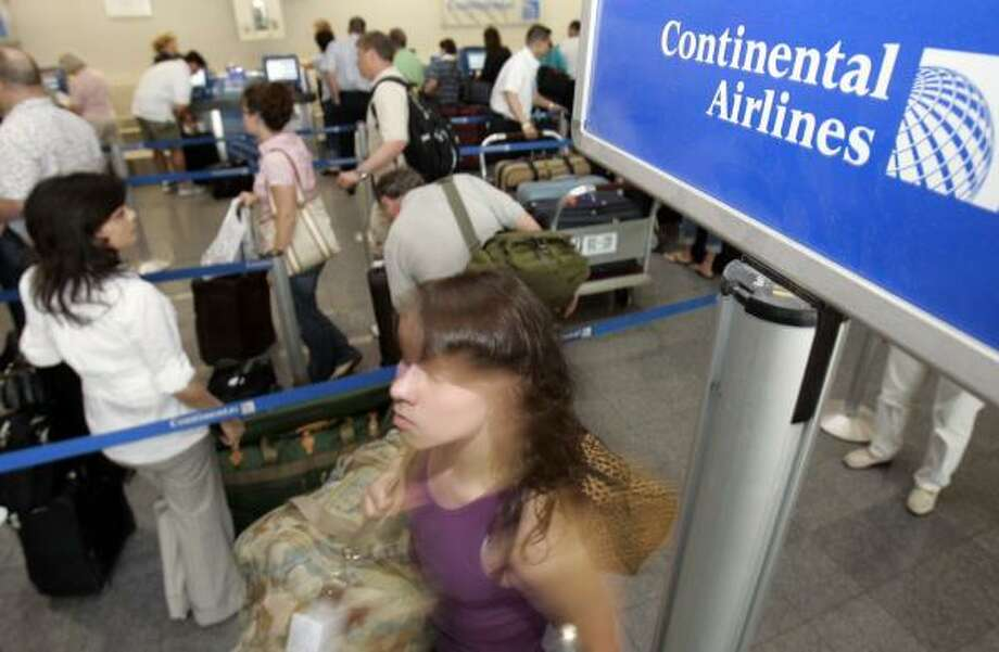 A Continental Airlines customer gets in line on Thursday at Cleveland Hopkins International Airport. The airline has yet to decide whether to charge passengers for a first bag. Photo: TONY DEJAK, ASSOCIATED PRESS