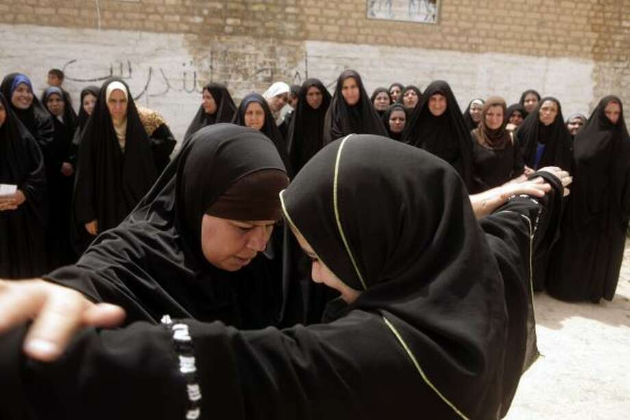Iraqi policewoman Kahlea Hassan Saeed, left,demonstrates proper search techniques to the Daughters of Iraq. Photo: MAYA ALLERUZZO, ASSOCIATED PRESS