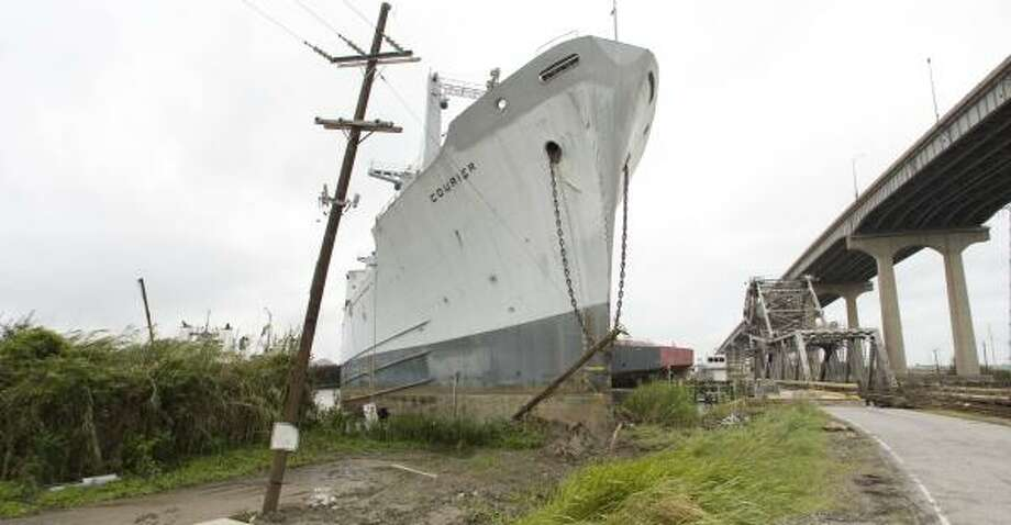 The storm surge shoved this cargo ship and several barges within yards of an I-10 bridge that leads to Slidell. Photo: BRETT COOMER, CHRONICLE