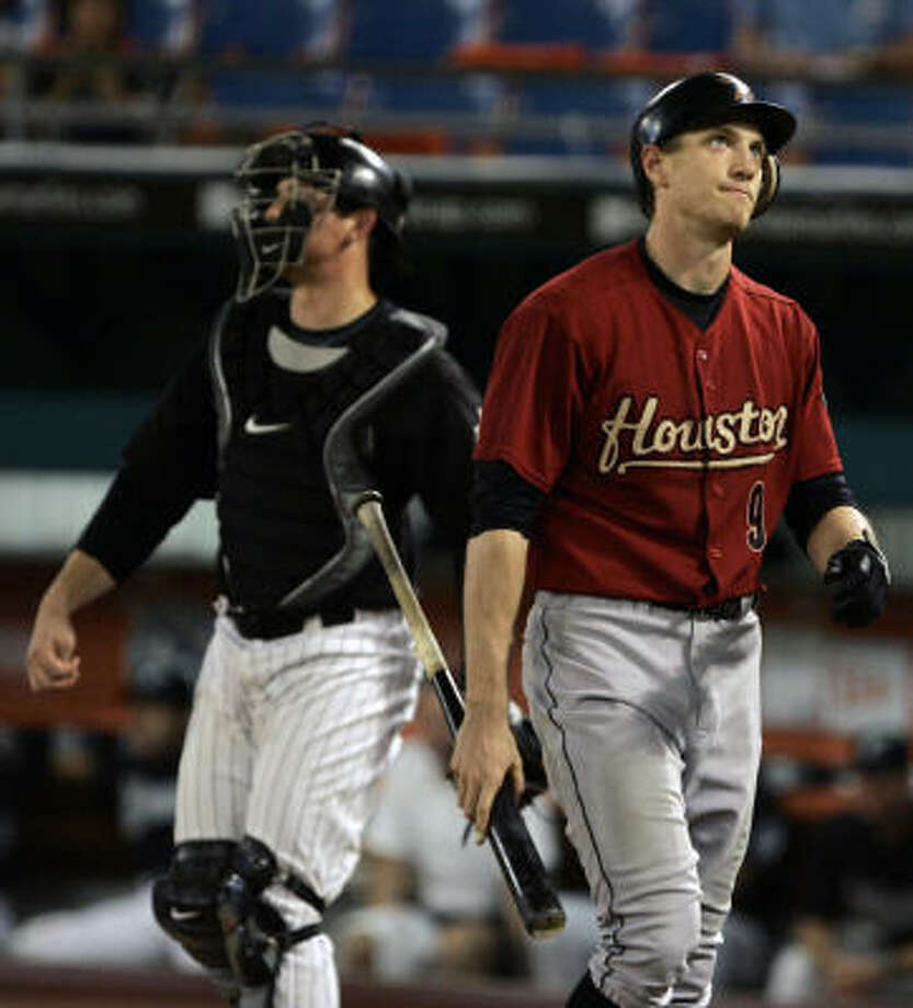 Hunter Pence, right, heads back to the dugout after he struck out swinging during the ninth inning against the Florida Marlins on Thursday at Dolphin Stadium in Miami. Marlins catcher John Baker, left, looks on. The Marlins defeated the Astros 8-1. Photo: Wilfredo Lee, AP
