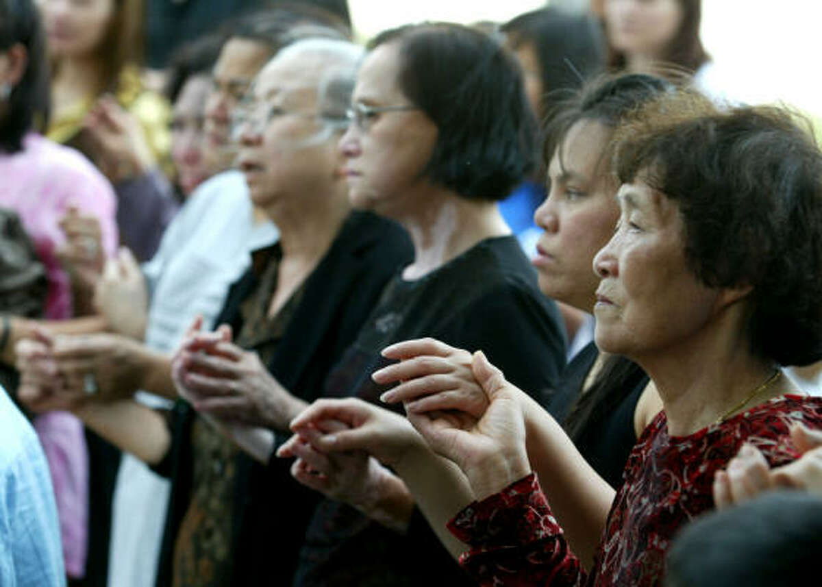 Vietnamese worshippers en route from the Marian Days festival in Missouri visit the bus crash site in Sherman on Sunday.