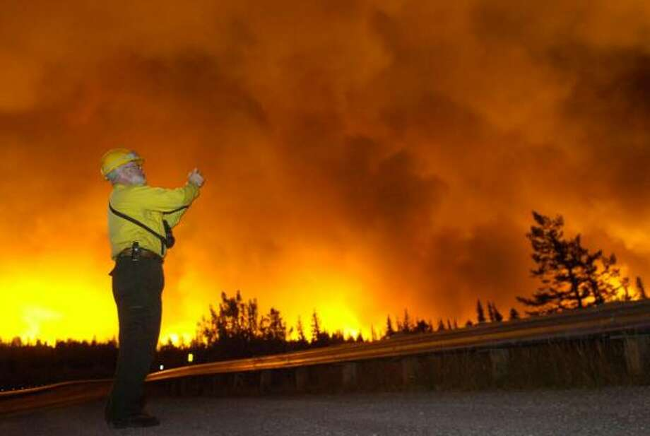 "Firefighters' spokesman Pat McKelvey snaps a photo of the wildfire in Montana's Glacier National Park, which he said could ""at least double"" in size. Photo: ROBIN LOZNAK, AP"