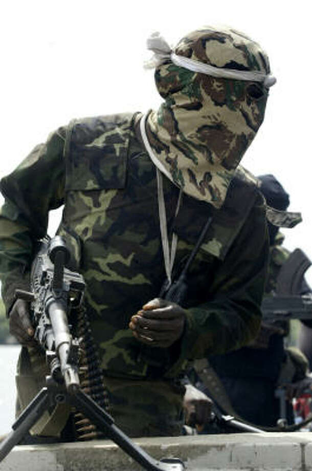 Nigerian militants, like this one patrolling the Niger Delta, have forced oil companies to pay more for employee insurance, salaries, perks and housing to keep thier workers in the country Photo: GEORGE OSODI, AP File